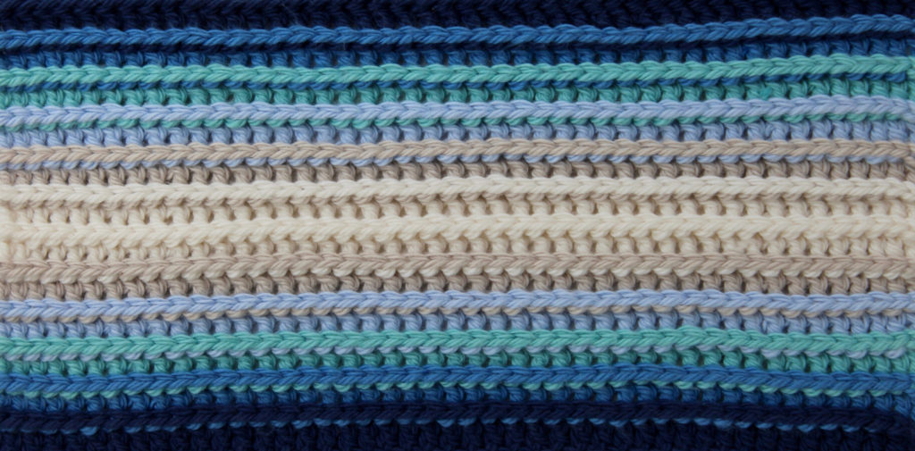 The textured background for my logo. Bendigo Woollen Mills 8 ply cotton in Parchment, Latte, Blue, Light Teal, Sky and French Navy.