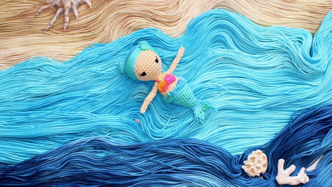 Amigurumi mermaid floating on an ocean made of yarn.
